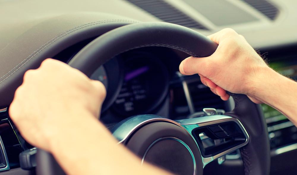 Hombre mostrando cómo se debe agarrar el volante correctamente