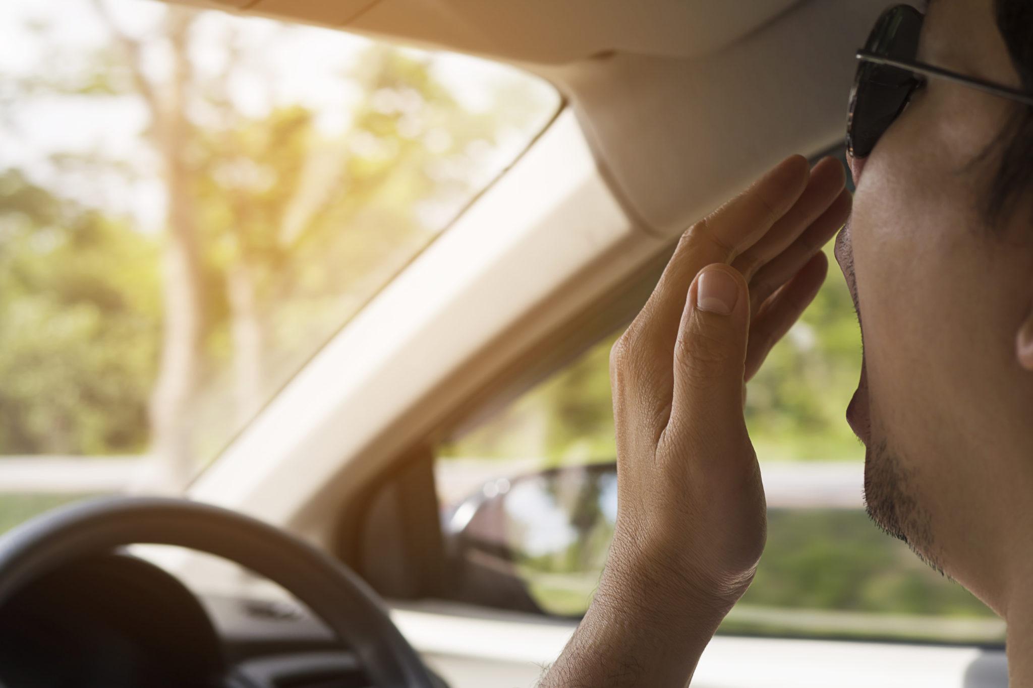 Hombre bostezando en coche